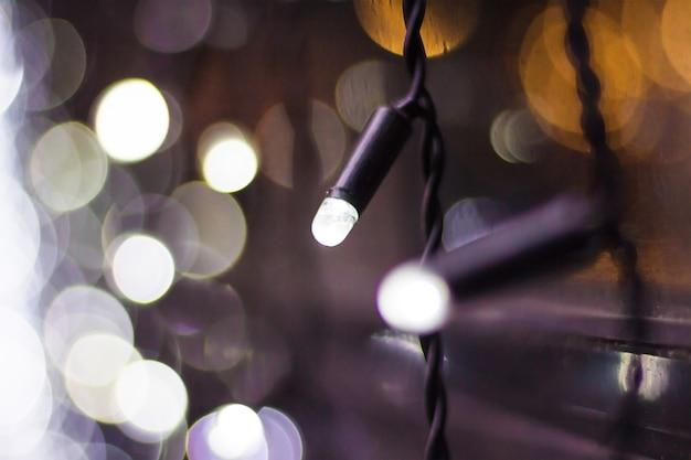 ボケ味のクリスマスライト。白い花輪のクローズアップ