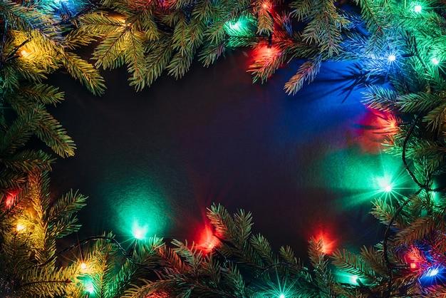 モミの木とクリスマスライト。黒の背景に装飾的なフレーム。フラットレイ、上面図、コピースペース