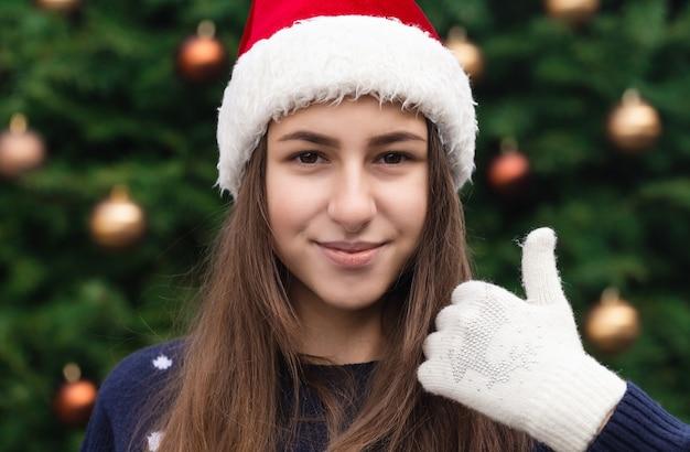 親指を立てるようなクリスマス。感情を込めてサンタクロースの帽子をかぶっている女性の肖像画をクローズアップ。クリスマスツリーを背景に。