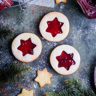 Christmas linzer cookies with raspberry jam on green table background.