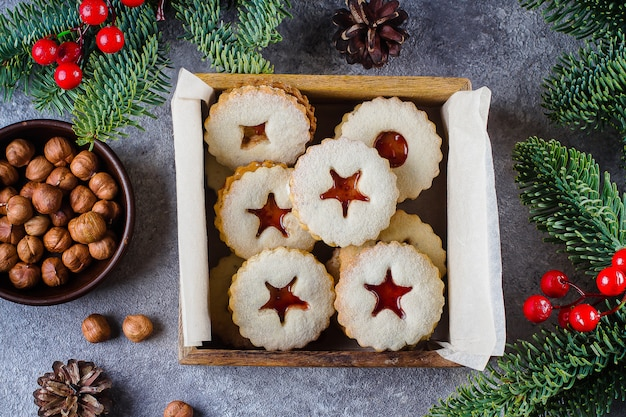 Christmas linzer cookies with red berry jam on gray concrete table background