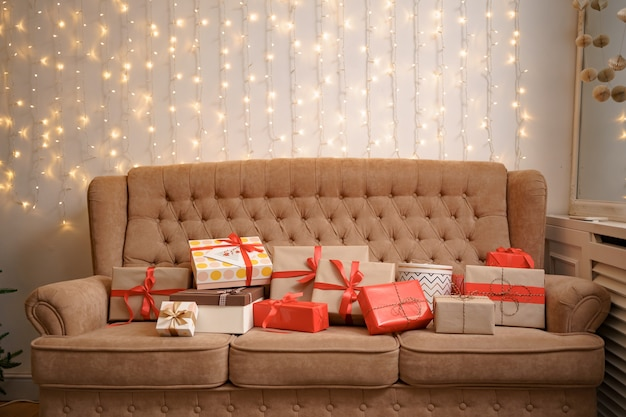 Christmas living room with a christmas tree and presents on the sofa