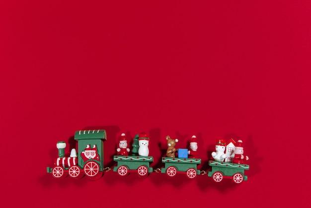 赤い背景の上のクリスマス機関車のおもちゃ
