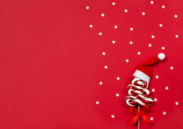 Рождественский леденец в форме елки с красной шляпой санты на красном, вид сверху
