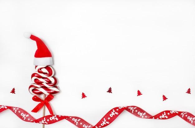 Рождественский леденец в форме елки с красной шляпой санта-клауса на белом, плоская планировка