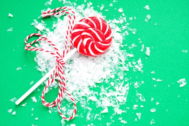 Christmas lollipop and snow on green. flat lay. new year and christmas sweets