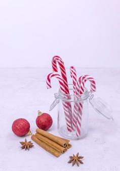 ガラスの瓶のシナモンスティックと赤いクリスマスボールのクリスマスロリポップ