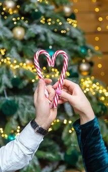 Рождественские леденцы в руках мужчины и женщины. выборочный фокус. праздничный день.