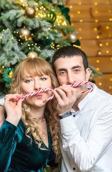 男性と女性の手にクリスマスロリポップ。セレクティブフォーカス。ホリデー。