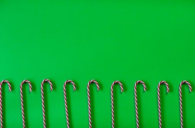 Рождественские леденцы на палочке на зеленом фоне. вид сверху.