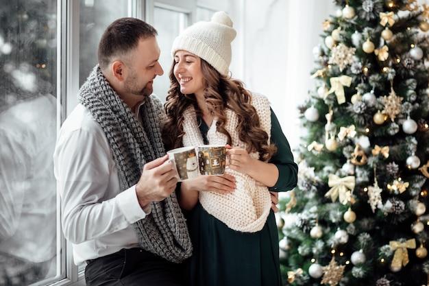 Рождество. любовь. главная. молодая пара в теплой одежде держит чашки, разговаривает и смеется, сидя дома возле елки.