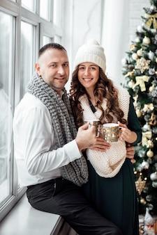 Рождество. любовь. главная. молодая пара в теплой одежде держит чашки,
