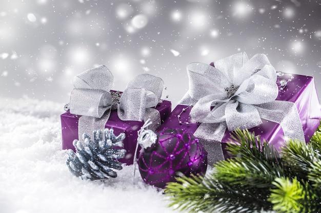 雪と抽象的な雪の雰囲気の中でクリスマスの豪華な紫色の贈り物。
