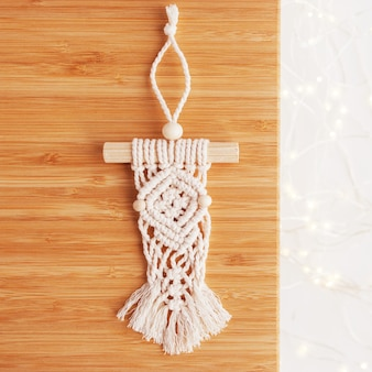 Christmas macrame decor. christmas panel on wooden board. natural materials - cotton thread, wood beads and stick. eco decorations, ornaments, hand made decor. winter and new year holidays. copy space