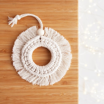 Christmas macrame decor. christmas ringl on wooden board. natural materials - cotton thread, wood beads and stick. eco decorations, ornaments, hand made decor. winter and new year holidays.