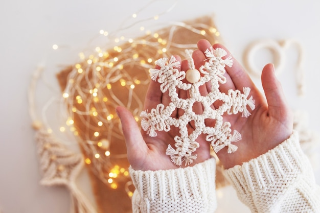 Christmas macrame decor. christmas snowflake on  background with blur lights. natural materials - cotton thread. eco decorations, ornaments, hand made decor. winter and new year holidays.