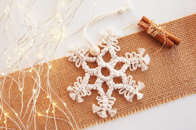 Christmas macrame decor. christmas snowflake on lockram. natural materials - cotton thread, wood beads. eco decorations, ornaments, hand made decor. winter and new year holidays