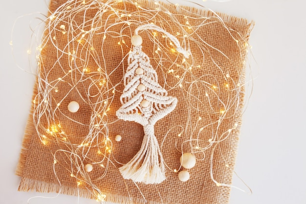 Christmas macrame decor. christmas tree on lockram. natural materials - cotton thread, wood beads. eco decorations, ornaments, hand made decor. winter and new year holidays.