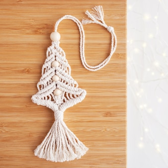 Christmas macrame decor. christmas tree on wooden board. natural materials - cotton thread, wood beads. eco decorations, ornaments, hand made decor. winter and new year holidays. copy space