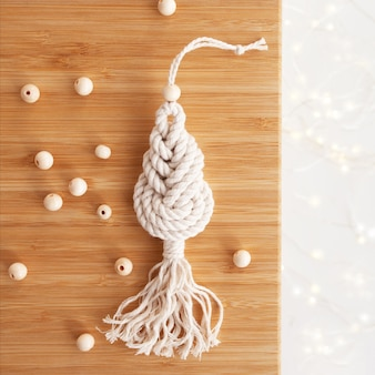 Christmas macrame decor. christmas tree on wooden board. natural materials - cotton thread, wood beads. eco decorations, ornaments, hand made decor. winter and new year holidays.