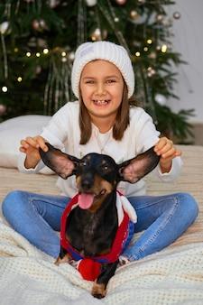 クリスマスの魔法のおとぎ話。小さな女の子が彼女の友人、ダックスフント犬と一緒に笑っています