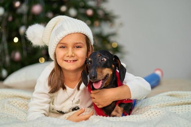 クリスマスの魔法のおとぎ話。小さな女の子がクリスマスツリーの近くで、友人のダックスフント犬と一緒に笑っています