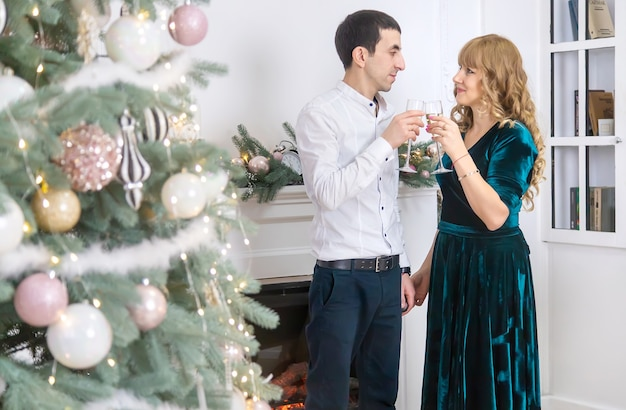 シャンパンのグラスを持つクリスマスの男性と女性。セレクティブフォーカス。ホリデー。