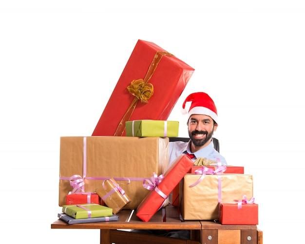 Рождественский мужчина в своем кабинете с несколькими подарками