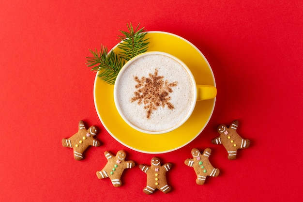 Christmas man-shaped gingerbread around yellow mug of coffee on red background