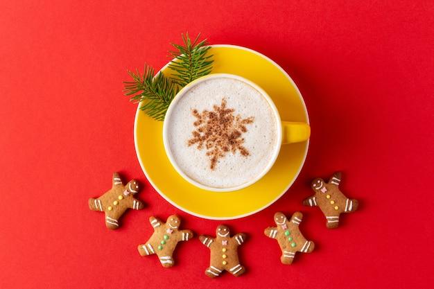 Рождественские пряники в форме человека вокруг желтой кружки кофе на красном фоне