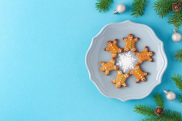 Рождественские пряники в форме человека на тарелке возле еловых веток на синем фоне