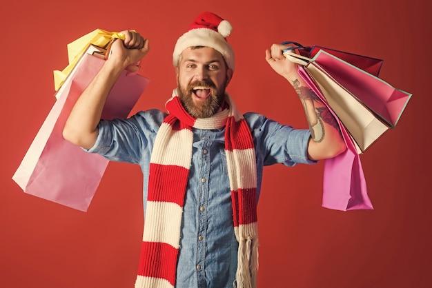 サンタの帽子とスカーフのクリスマスの男の買い物客