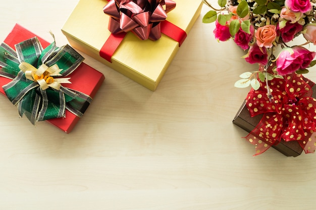 Christmas many gifts with rose vase and on wooden interior of top view. decoration during christmas and new year.