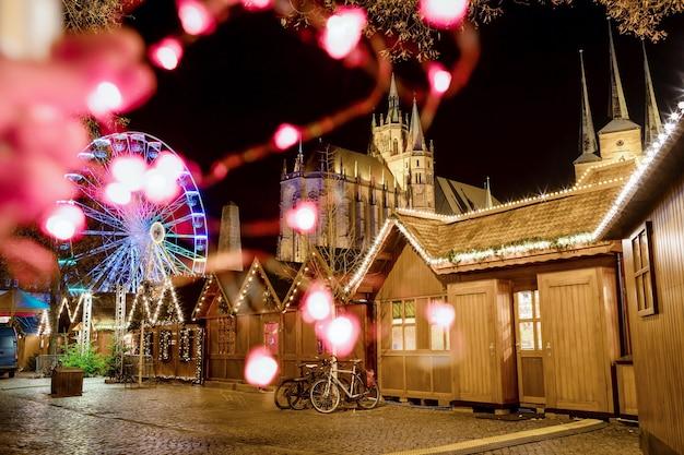 エアフルトドイツの夜のクリスマスマーケットの観覧車と有名な大聖堂のドームの丘