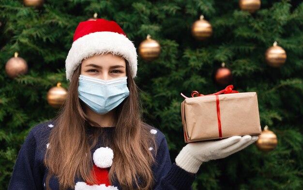 Рождественские маски поздравления. портрет женщины в шляпе санта-клауса и синем свитере в медицинской маске, дарит подарочную коробку с красной лентой, боке рождественской елки на фоне