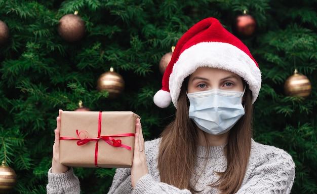 Рождественские маски поздравления. портрет женщины в шляпе санта-клауса и свитере в медицинской маске, дарит подарочную коробку с красной лентой, рождественскую елку боке на фоне
