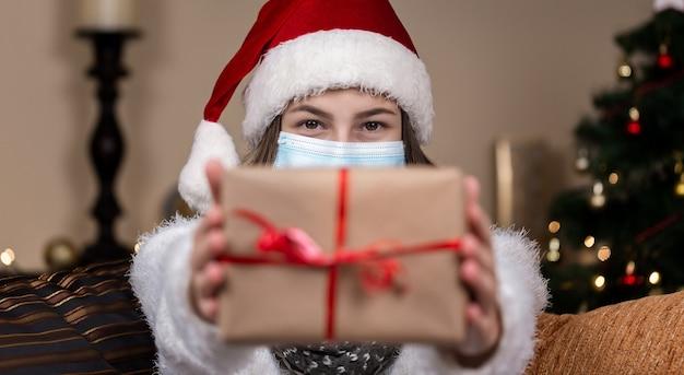 Рождественские маски поздравления. портрет женщины в шляпе санта-клауса и белом свитере в медицинской маске, дарит подарочную коробку с красной лентой, боке рождественской елки на фоне
