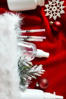 Рождественский медицинский коронавирус плоской планировки, защитная маска для лица, таблетки, антисептики, украшение на красном фоне, новогодняя тема, вид сверху, минимализм, плоский макет, covid и концепция с новым годом