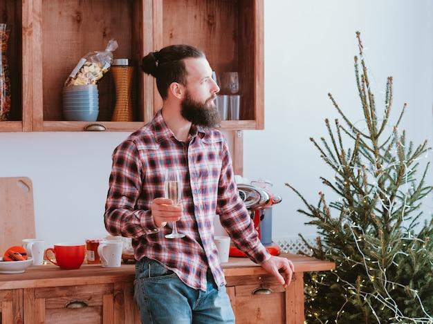 Рождественская меланхолия. задумчивый хипстерский парень пьет шампанское на кухне, глядя в окно Premium Фотографии