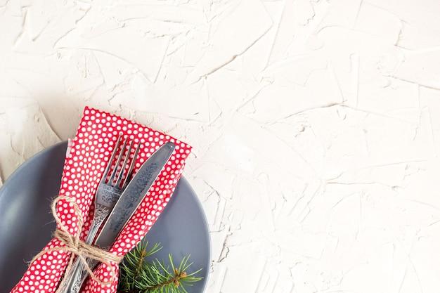 白いテーブルの上のフォークナイフナプキンとモミの木のブランチとクリスマスメニューの背景。コピースペース、上面図。