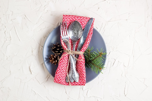 Christmas menu background with fork knife napkin and fir tree brunch on white table. copy space, top view