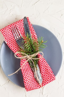 Christmas menu background with fork knife napkin and fir tree brunch on white table. top view