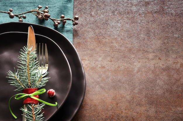 Christmas menu concept with decorated black plates and cutlery