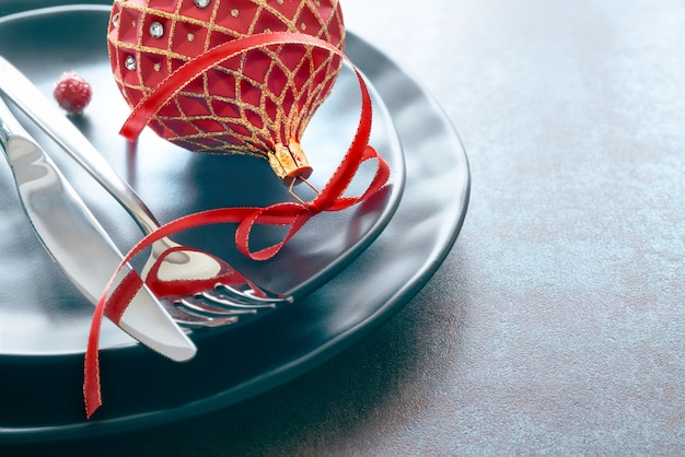Christmas menu setting with black plates and cutlery decorated with red christmas trinket and ribbon