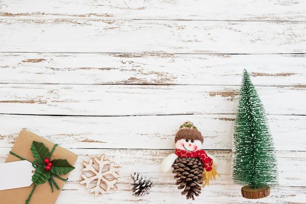 白い木製の背景にクリスマスミニチュアツリー、クリスマスの装飾、ギフトボックス。ビンテージスタイル、トップビュー。