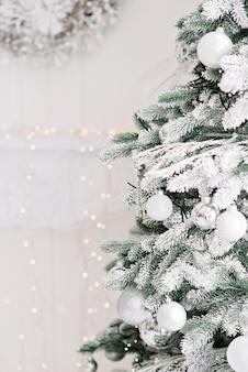 クリスマスの最小限の背景、ぼやけたボケ光の背景にボールで飾られたクリスマスツリー
