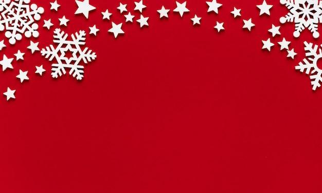 赤い背景の上の白い木製の雪片と星のクリスマスの最小限の構成。フラットレイ、上面図。