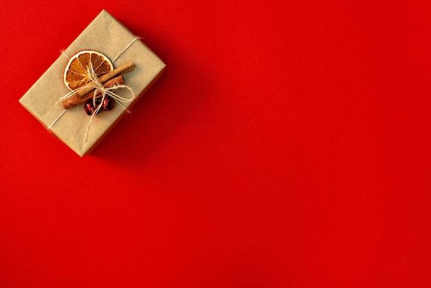 Рождественская минимальная композиция. подарочная коробка, украшение на красном фоне. плоская планировка, вид сверху, копия пространства.