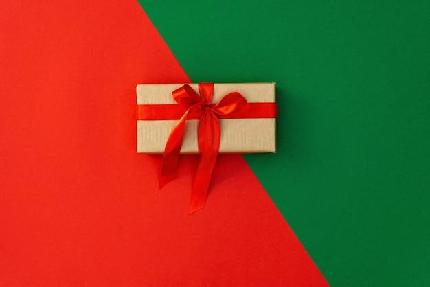Рождественская минимальная композиция. подарочная шкатулка с атласным бантом, украшения на красно-зеленом фоне. плоская планировка, вид сверху, копия пространства.