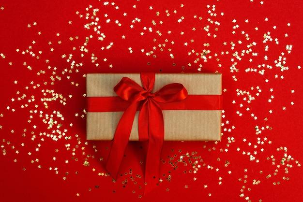 Рождественская минимальная композиция. подарочная коробка для поделок с атласным бантом, с блестками звезд на красном фоне. плоская планировка, вид сверху, копия пространства.